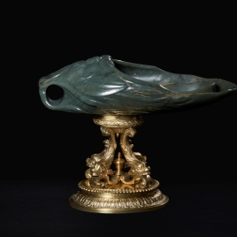 Jade vessel in the form of a mask on four dolphins