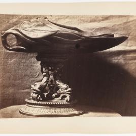 Vaso de jade en forma de mascarón, sobre cuatro delfines