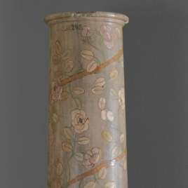 Grey marble column with floral decoration